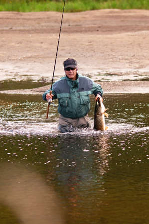 pike: Fisherman with pike fish on the shore of river Uur in northern Mongolia Stock Photo