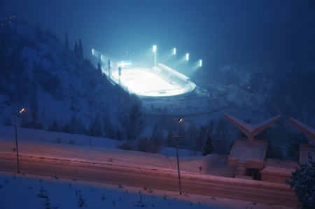Huge ice skating rink in thick fog at sunset. Kazakhstan, Medeo is an outdoor speed skating and bandy rink, located in a mountain valley photo