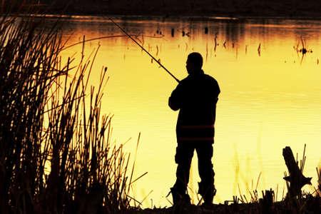 horgász: Fisherman sziluett napkeltekor