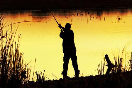 hombre pescando: Pescador silueta en el amanecer Foto de archivo