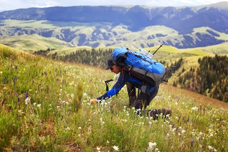 Hiker stopping to smell the wildflowers photo