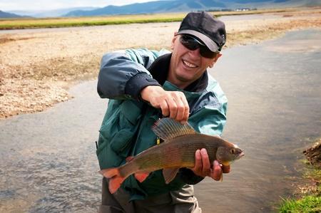 grayling: Pescador con t�malo peces en la orilla del r�o Ider en el norte de Mongolia Foto de archivo