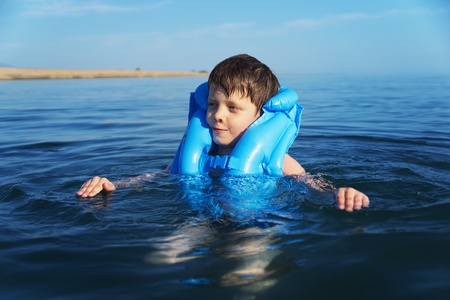lifejacket: Smiling boy swimming in the life jacket