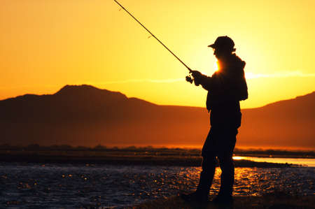 trout fishing: Fishing in the Mongolia - fisherman silhouette Stock Photo