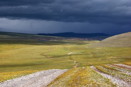 rough road: Roads in the desert steppes of Mongolia,village on the horizon and the storm sky