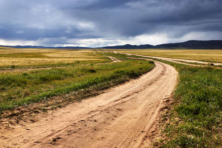 rough road: Roads in the desert steppes of Mongolia and the storm sky