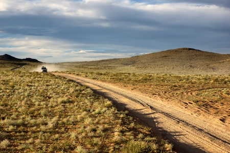 rough road: Roads in the desert steppes of Mongolia and car on the horizon