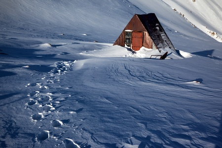 An abandoned hut in mountains of winter photo