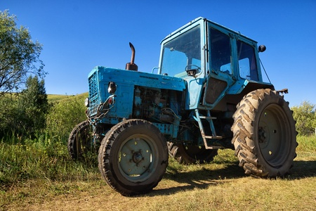 wheeled tractor: Blue wheeled agricultural tractor, dusty and rusty