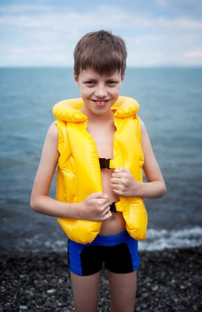 lifejacket: Smiling boy in the life-vest beside water Stock Photo