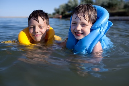 lifejacket: Smiling brothers swimming in the life jacket