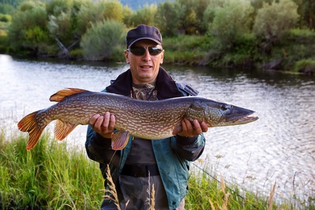 anglers: Fisherman with pike fish on the shore of river Uur in northern Mongolia Stock Photo