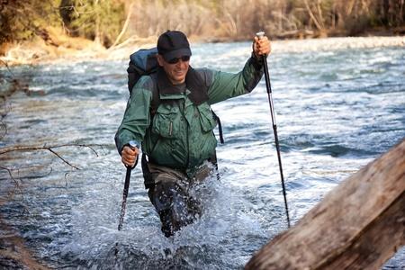 rugged terrain: Backpacker wade rugged mountain river Editorial