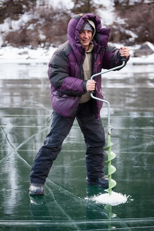 Ice fisherman drill on  winter mountain lake  photo