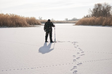 ice fishing: Ice fisherman drill on winter lake  Stock Photo