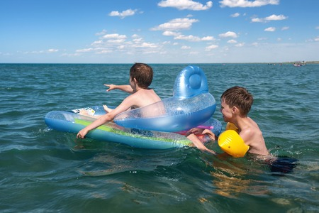 lifejacket: Two brothers swimming in inflatable boat Stock Photo