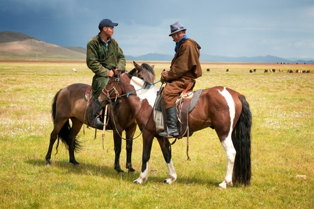 mongolia: NORTHERN MONGOLIA , MONGOLIA - AUG 06, 2011: Mongolian herders pose for foreign tourists