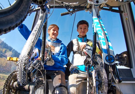 ALMATY REGION, KAZAKHSTAN - OCT 13, 2013: Young sportsmen  S.Kuznetcov (N60) and A.Bospaev (N54) in the cable car, rise to the start of the competition at mountain bike sports event Red Bull Mountain Rage.
