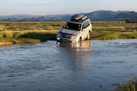 4 wheel: WESTERN MONGOLIA, MONGOLIA - AUG 13, 2012: Foreign tourists in cars crossing small river.