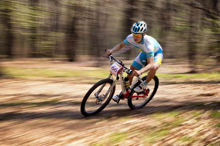 bikecross: ALMATY, KAZAKHSTAN - APRIL 19, 2014: K.Kazatncev (N66) in action at cross-country competition Open season - Bikes relay 2014