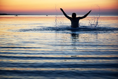 swimming silhouette: Silhouette of a male jumping with raised arms in the water  Stock Photo