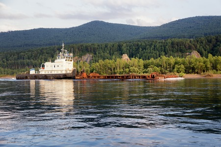 mining ship: KRASNOYARSK REGION, RUSSIA - JULY 10, 2014: Tugboat named Hero Moskvin pulling a barge on the Yenisei River