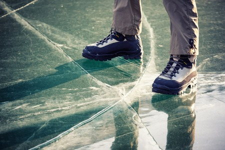 cracking: Legs in boots on the cracking ice Stock Photo