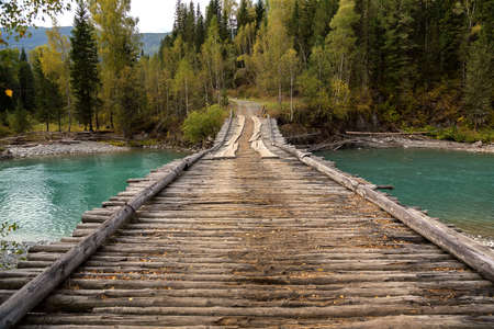 Old wooden bridge over river Belaya Berel in eastern Kazakhstan Stock Photo