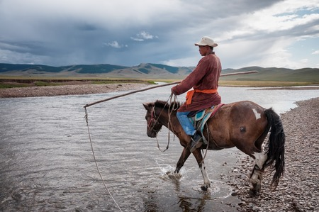 independent mongolia: NORTHERN MONGOLIA , MONGOLIA - AUG 06, 2011: Mongolian herder pose fording the river for foreign tourists