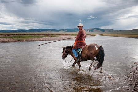 herder: NORTHERN MONGOLIA , MONGOLIA - AUG 06, 2011: Mongolian herder pose fording the river for foreign tourists