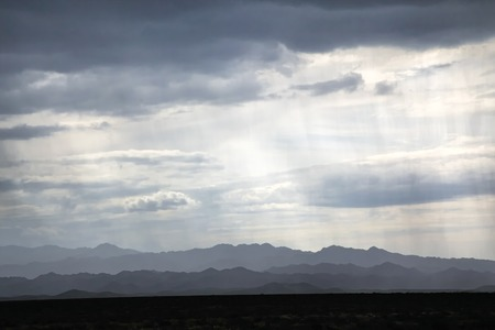 shroud: Shroud of of rain and silhouettes of desert mountains on the horizon. Note: low resolution because of rain.