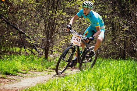 ALMATY, KAZAKHSTAN - APRIL 19, 2015: N.Jurbin (N14) in action at cross-country competition Open season - Bikes relay 2015