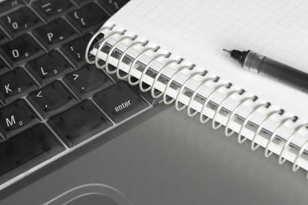 Close-up of a notebook and a pen on a semi-transperant laptop keyboard. Focus around the