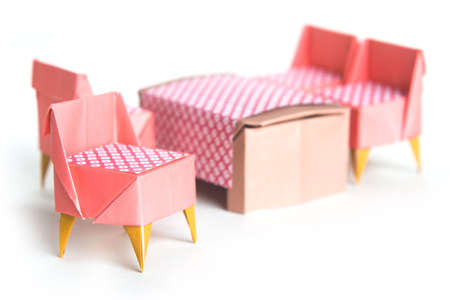 Origami chairs and table on a white background