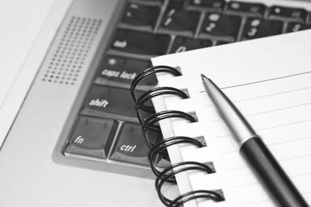 Close-up of a notebook and a pen on a semi-transparent laptop keyboard. Shallow depth of field. Stock Photo
