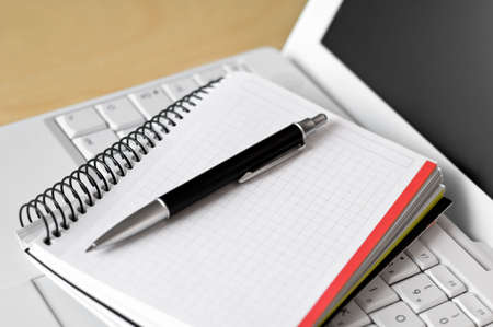 A laptop, a notebook and a pen on a desk. Shallow depth of field. Stock Photo - 3299888