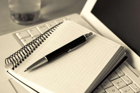 Photo of a laptop, pen, notebook and a glass of water, things that you often see in seminars and meetings. Stock Photo