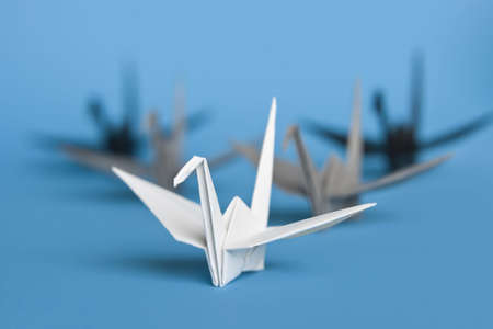 A group of five origami birds forming a v pattern