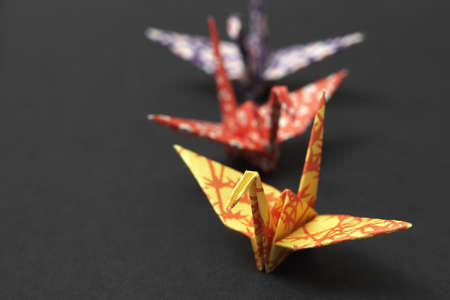 Three origami cranes on a black ground