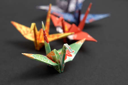 Five origami birds on a black background