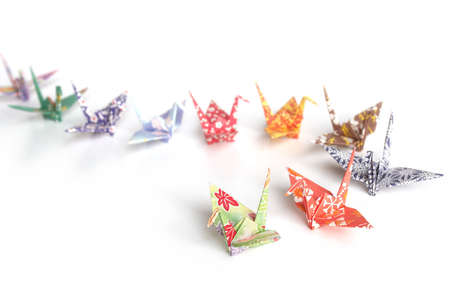 A queue of colourful origami birds on a white background