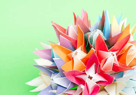 A colourful origami flower ball on a green background