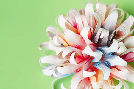 Multicolour origami flower ball on a green background Stock Photo