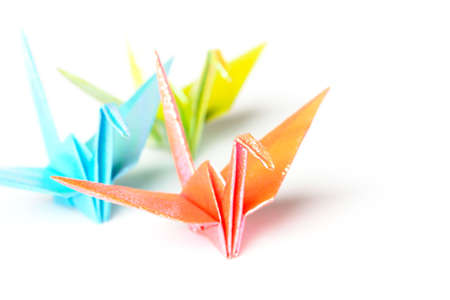 A group of 3 pastel colour paper birds on a white background  Stock Photo