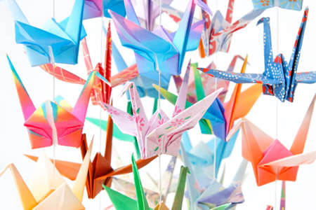 Multicolour paper cranes. Soft focus and shallow depth of field. Focus on the pink bird in the middle.  Stock Photo