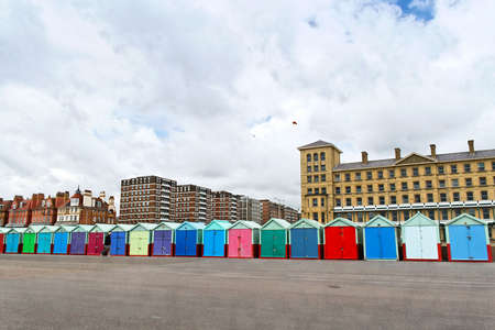 A roll of colourful beach huts along Kings Esplanade with Kings House behind on the right hand side