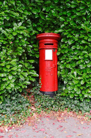An antique Victorian UK post pillar surrounded by green leaves  Stock Photo