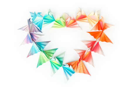 Colourful paper birds arranged in a heart shape on a white background