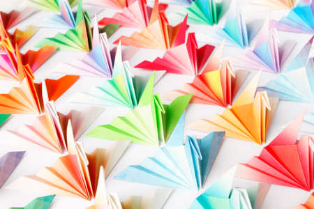 A group of colourful origami birds facing the same direction. High key soft focus.