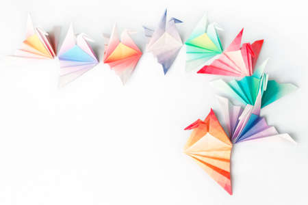A queue of colourful origami birds on a white background. High key soft focus.